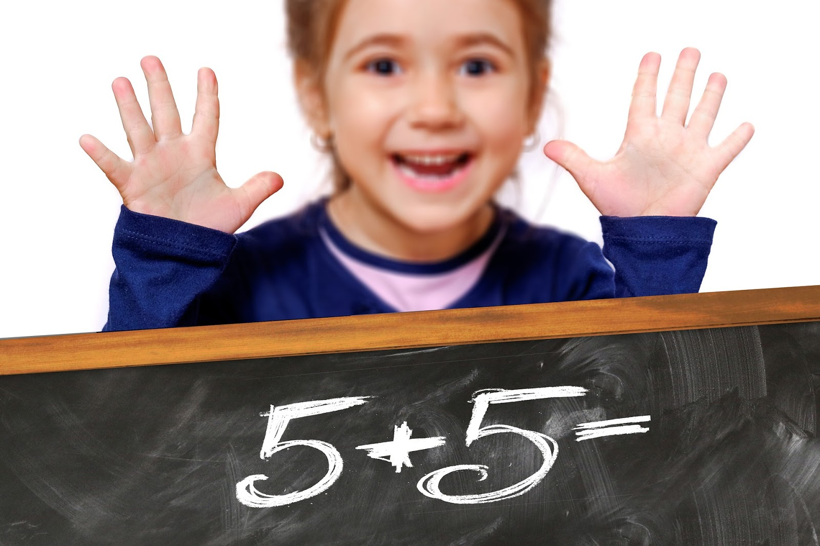 a child holds up all 10 fingers in front of a black board with a simple math problem
