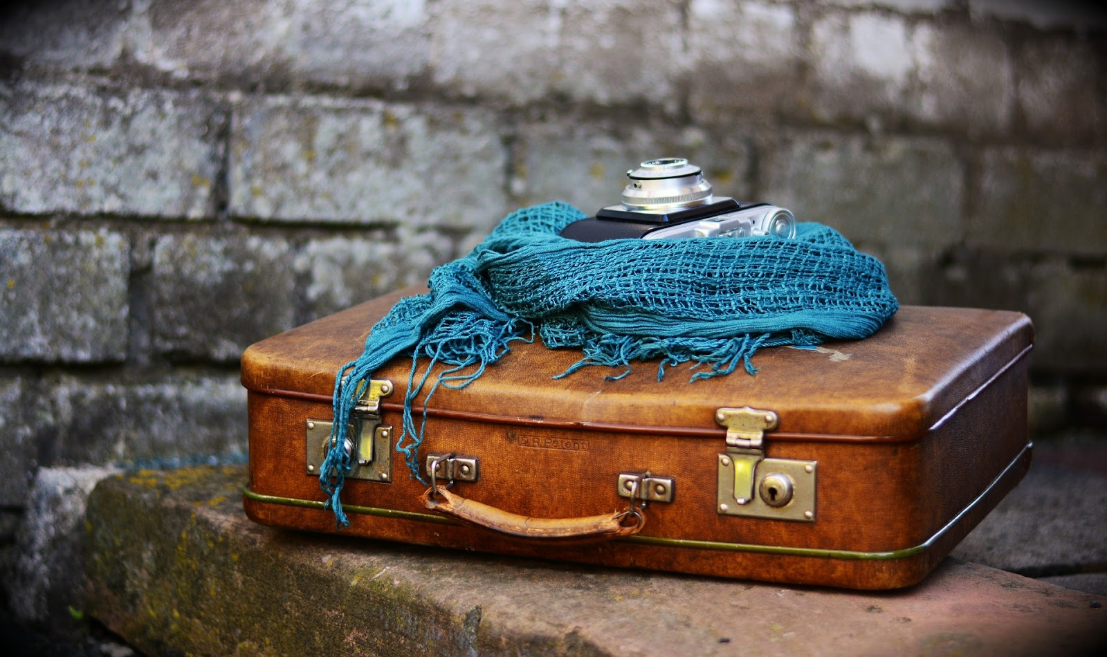 a camera and blue scarf sit on top of the leather suitcase of a world traveler