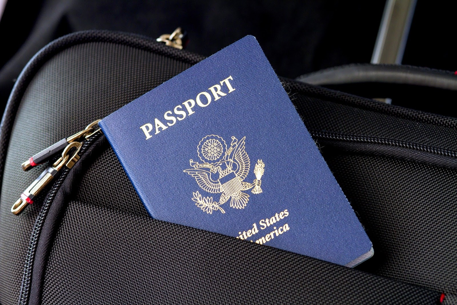 A passport sticking out of a black suitcase - the first step in learning how to travel abroad