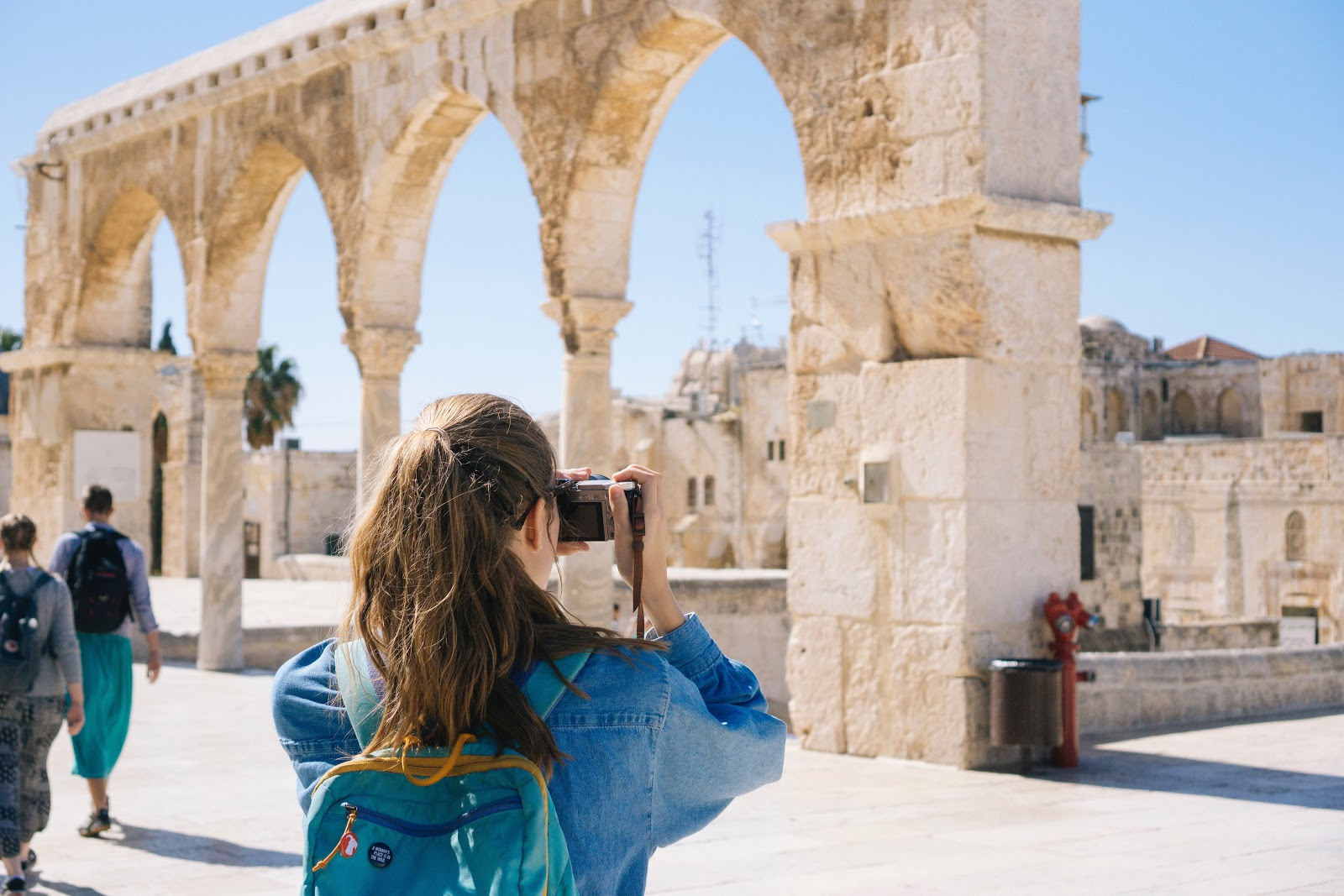 a young woman with a ponytail takes a photo of ancient ruins on her travels