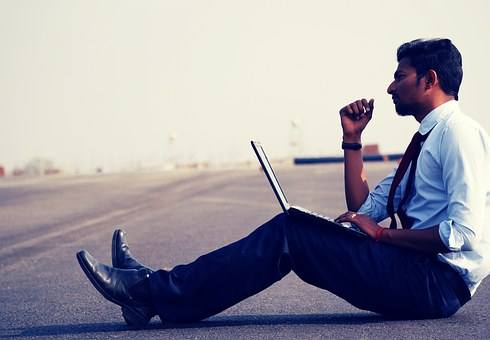 a man wondering how to change careers sits with his laptop on the ground