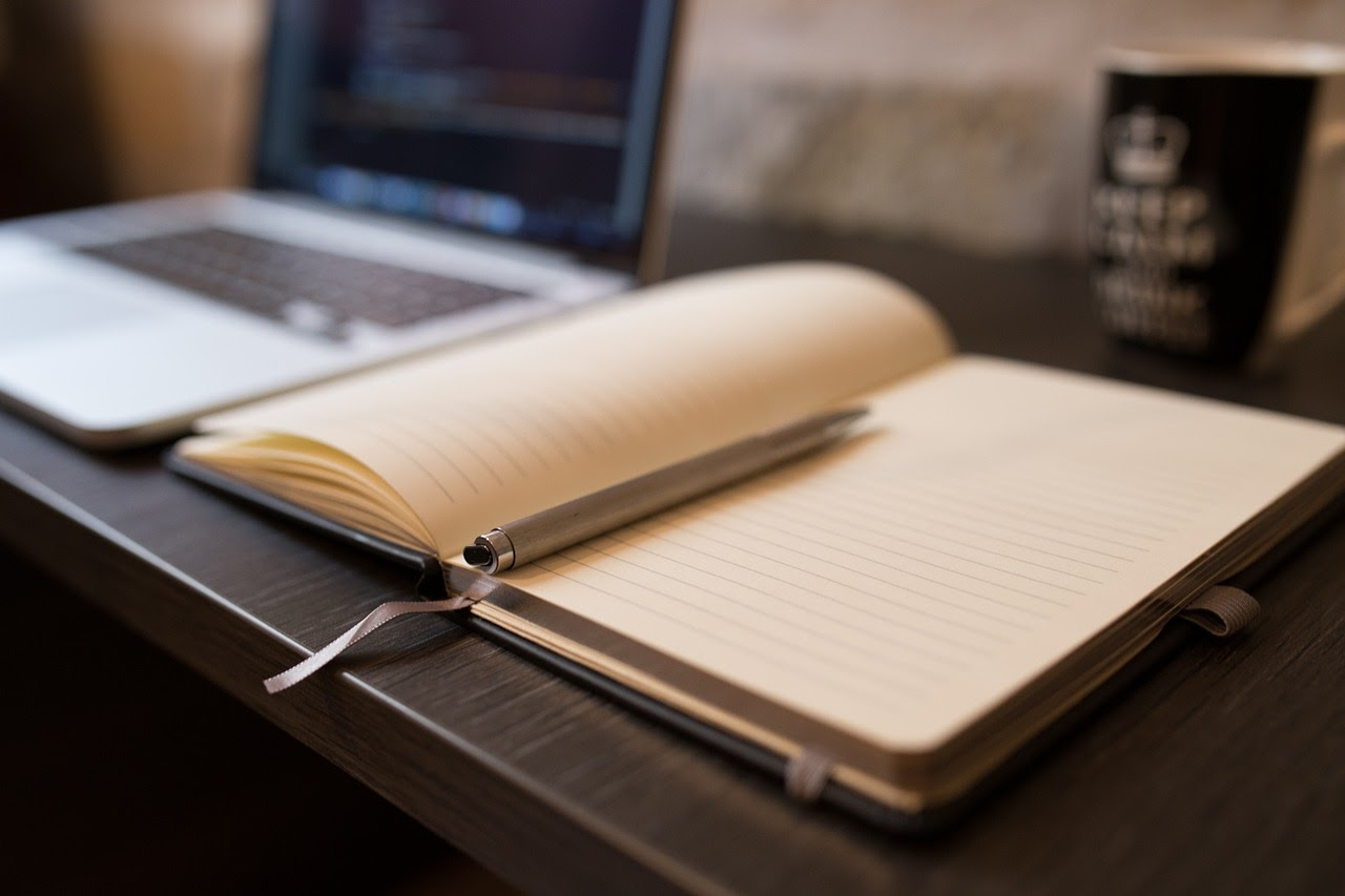 a notebook and pen that an adult has placed beside their laptop while learning how to journal