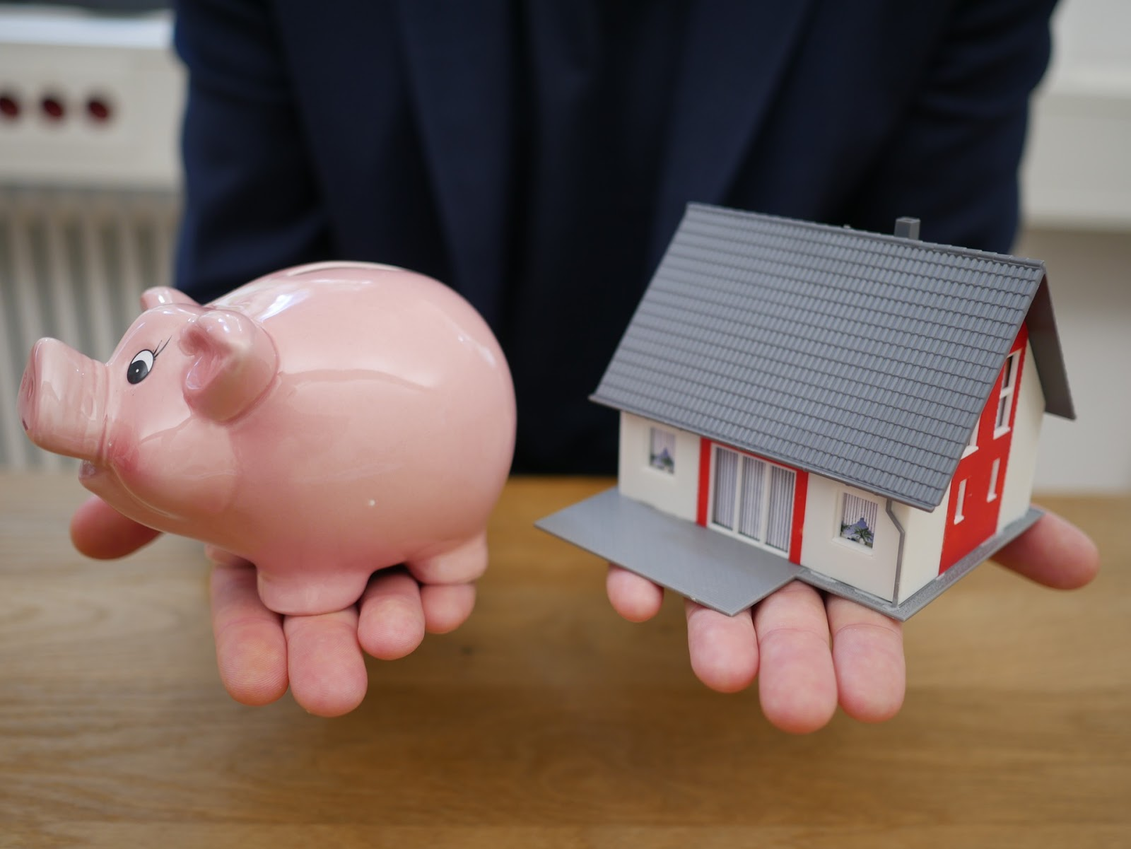 a young person learning how to adult holds a piggy bank in one hand and a model of a house in another