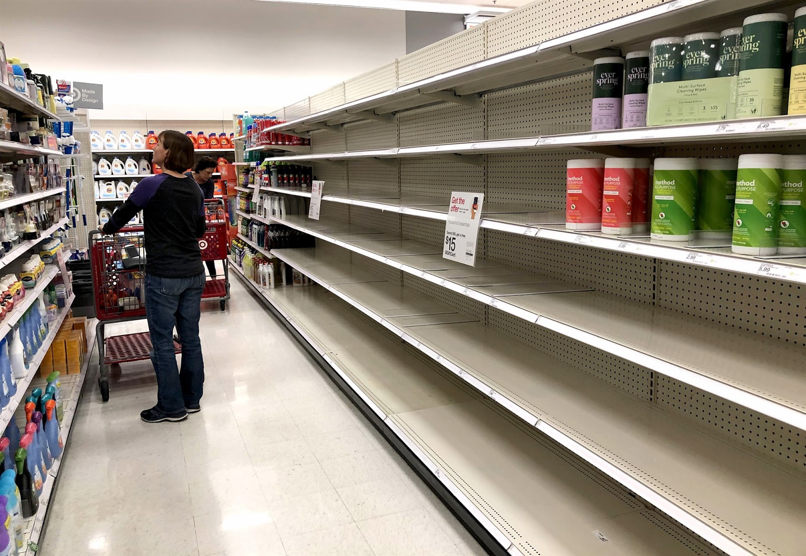 empty shelves in the disinfectant aisle of a grocery store after panic-buyers wipe out their stock