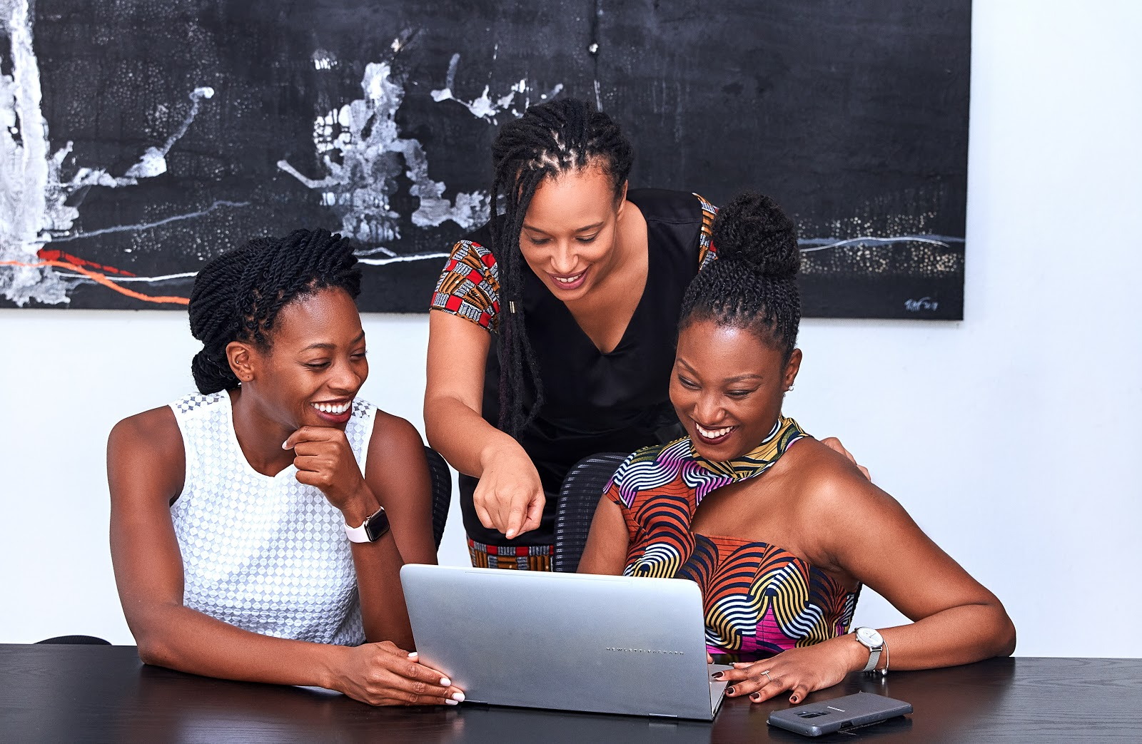 Three women gathered around a laptop computer
