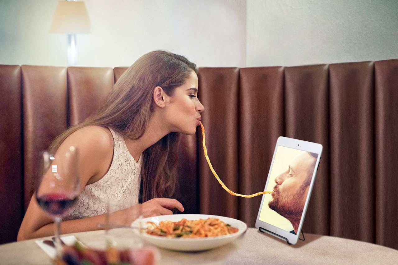Lady slurping a noodle and the other end on a screen with her partner