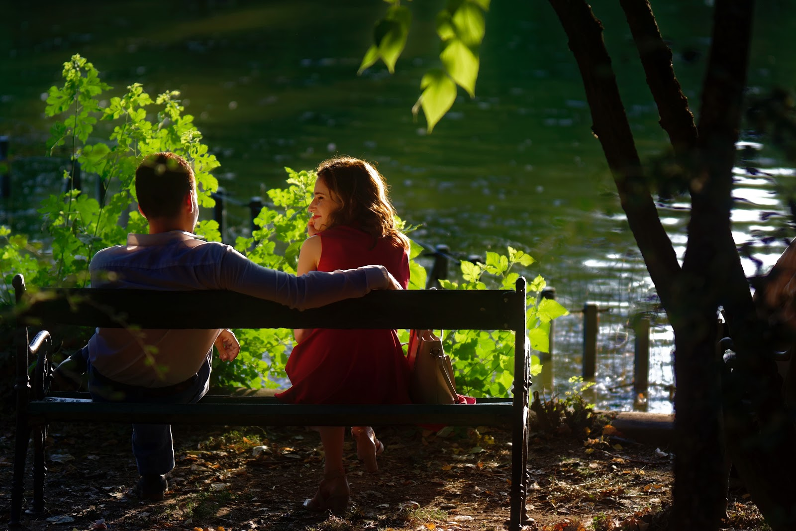 A couple sitting on a bench by a lake
