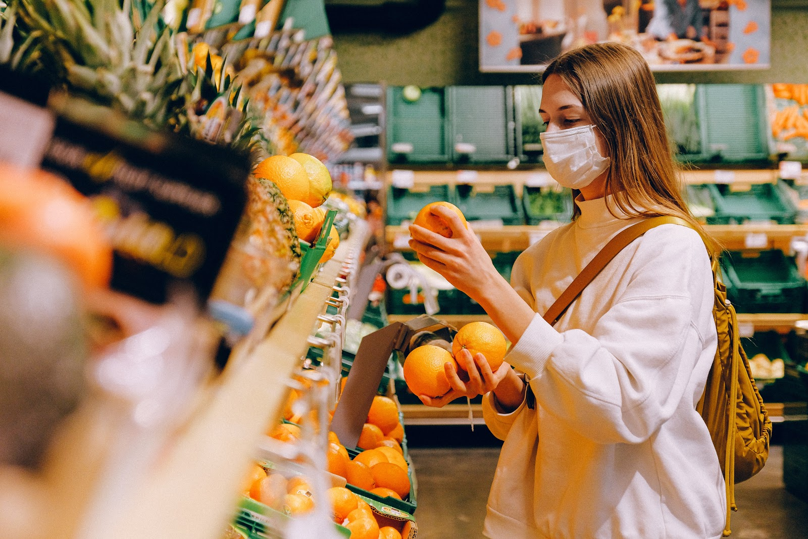 Lady at a grocery store wearing a mask shopping for oranges