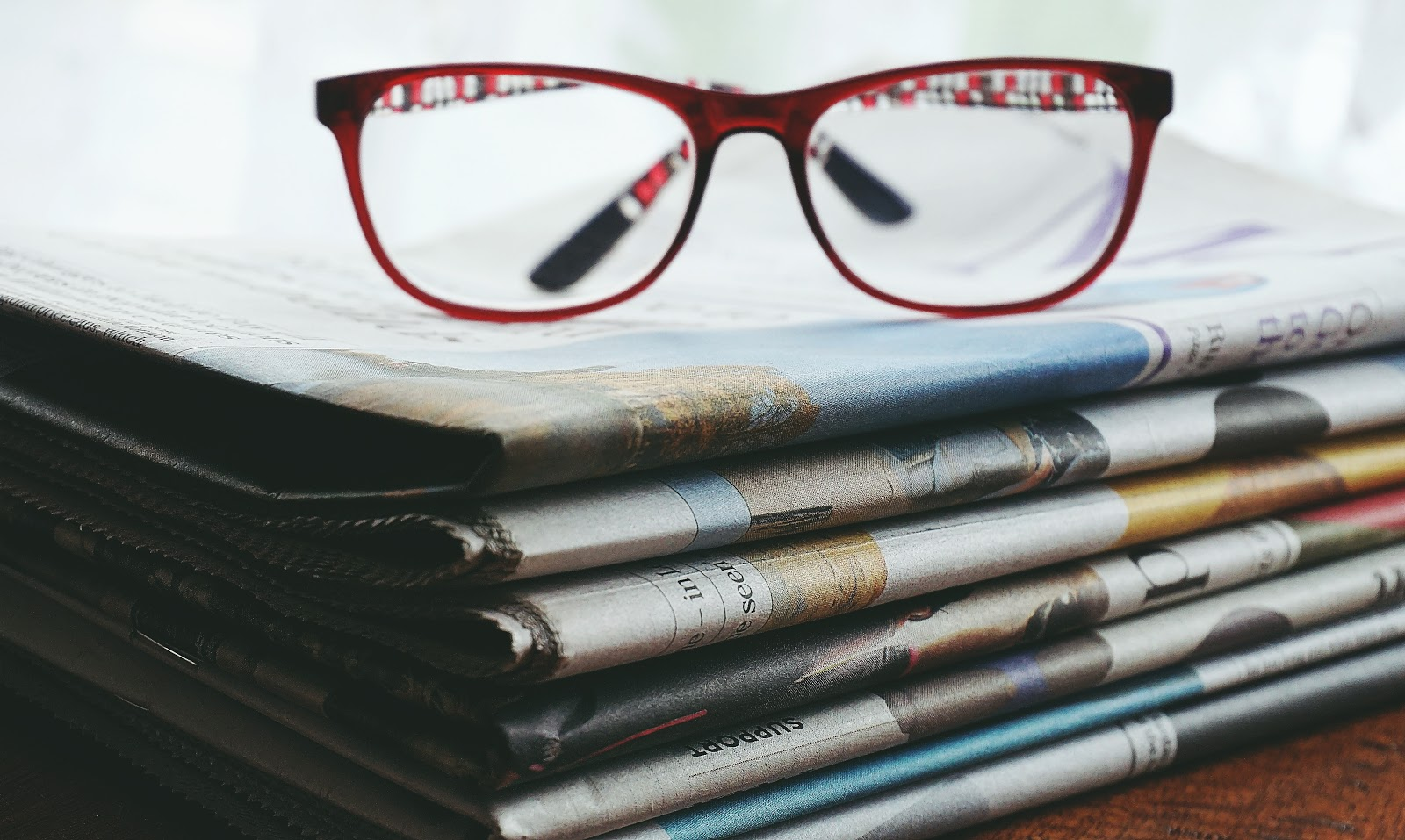 A stack of newspapers with a pair of glasses on top