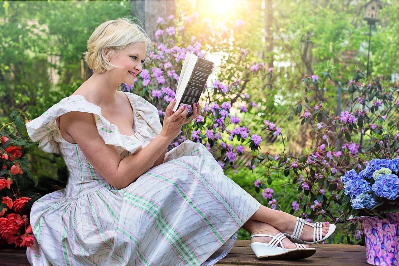 an adult woman reads a book in her garden