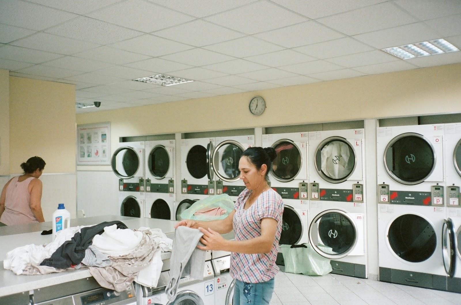 Lady folding laundry at a laundromat