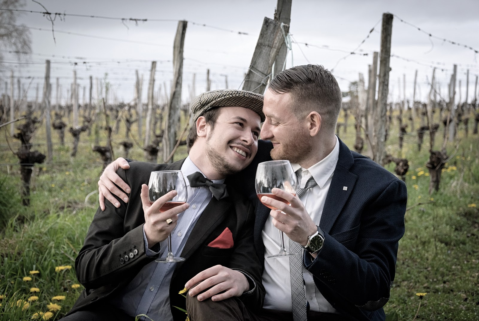 Two men in their 40s enjoy a date at a vineyard.