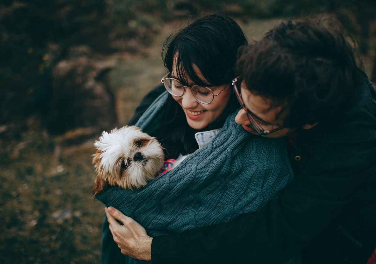 A couple in their 40s and 50s hug their dog.