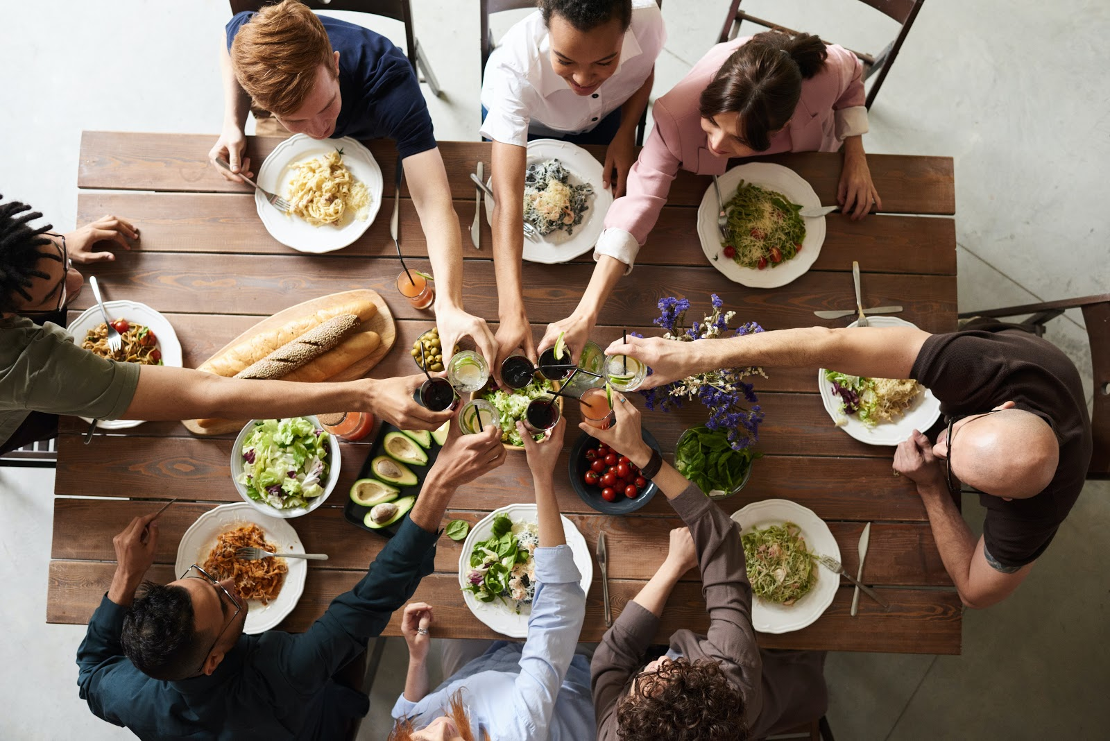 A group of friends in their 40s share a meal together.