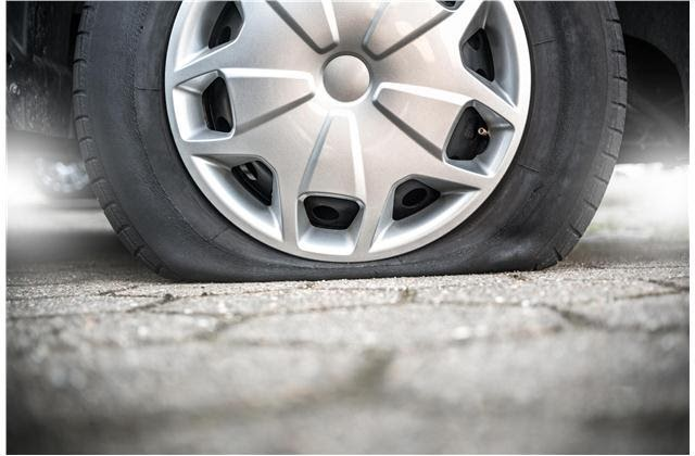 A flat tire close up with a hubcap on. Looks like its time to change the tire!