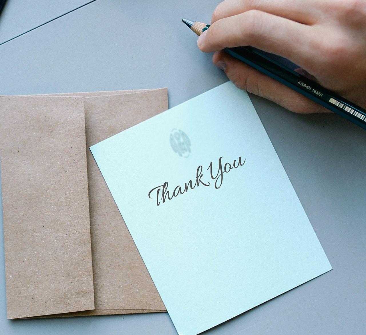 A blue thank you note with pencil poised over it