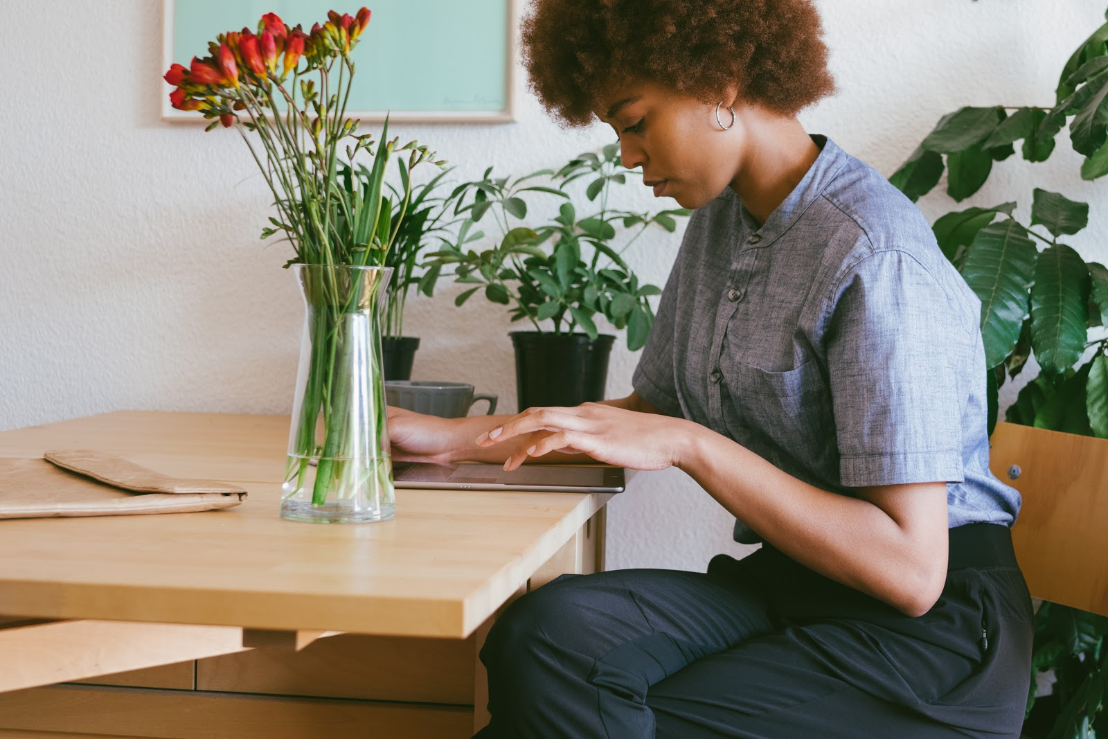 A woman surrounded by plants works on her laptop in her apartment.
