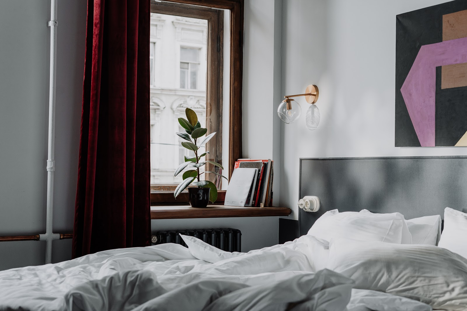 A bright, cozy bedroom with a plant in the window.