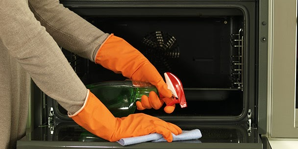 Person with gloves on and a spray cleaning their oven.