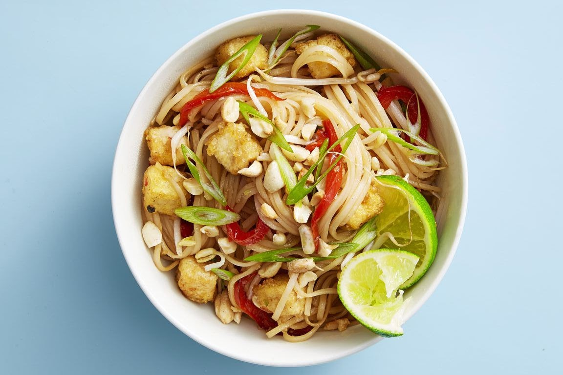 A bowl of tofu pad thai topped with peanuts and lime slices.