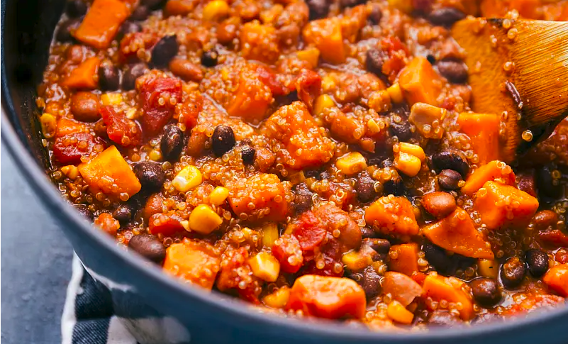 A pot of chili filled with quinoa, black beans, and sweet potatoes.