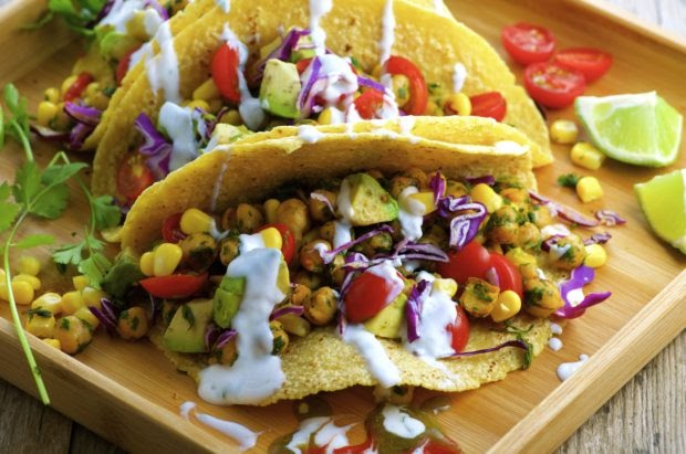 A plate of fresh tacos with corn, tomato, avocado, and protein from chickpeas.