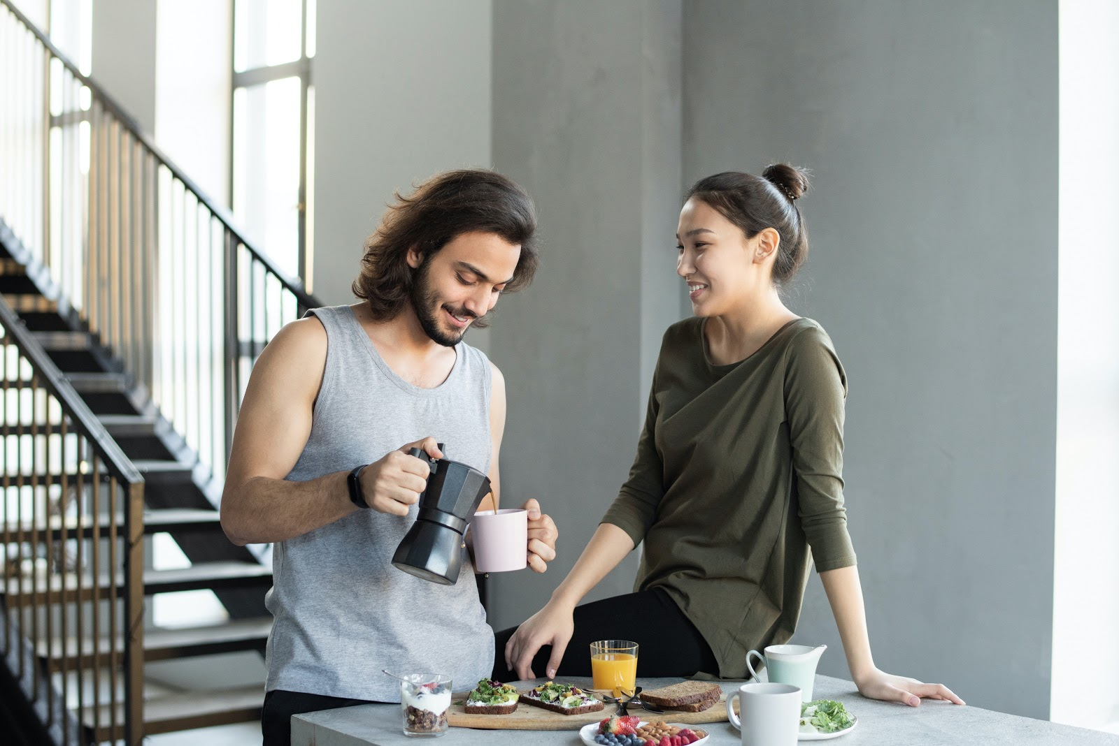 A happy couple drinks coffee at their breakfast table.