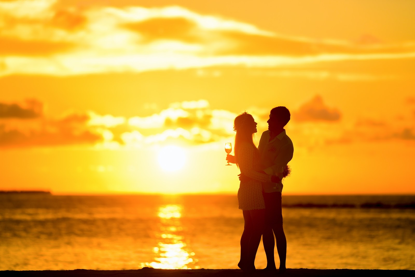 A couple hugs in front of a sunset on a beach.