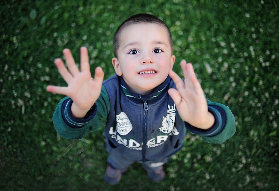 The camera looks down on a small boy against a grassy backdrop, his head tilted towards the camera