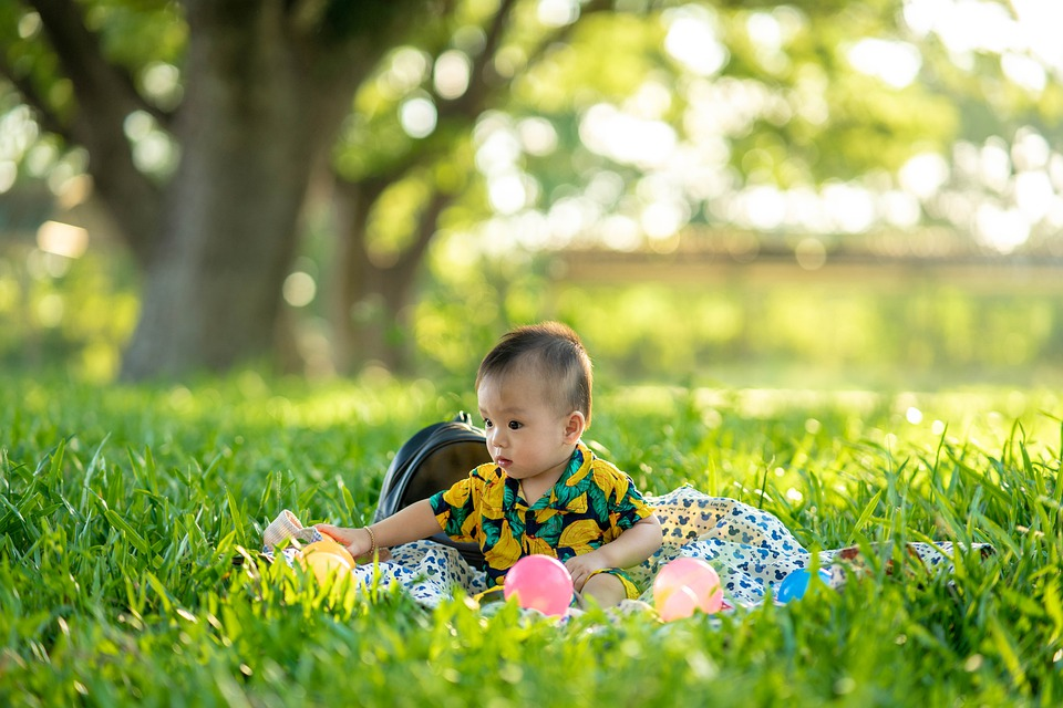A baby plays with colorful toys in the grass