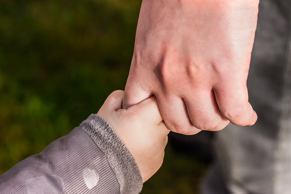 A close up of child and adult holding hands