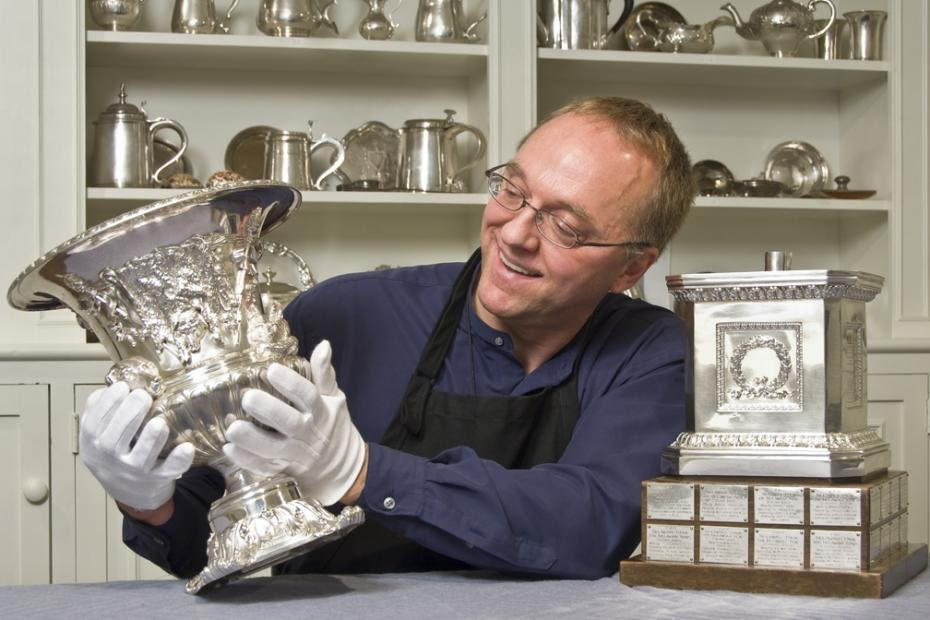 Smiling conservator from the Winterthur museum polishing a silver object.
