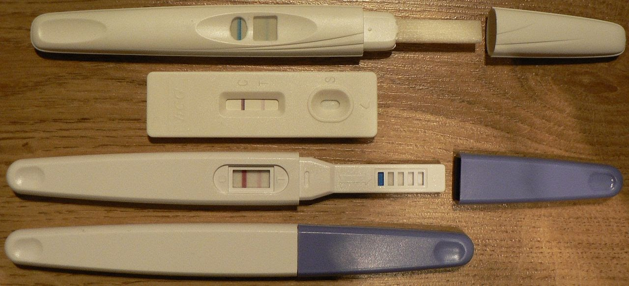 Four different pregnancy tests sitting on a table.
