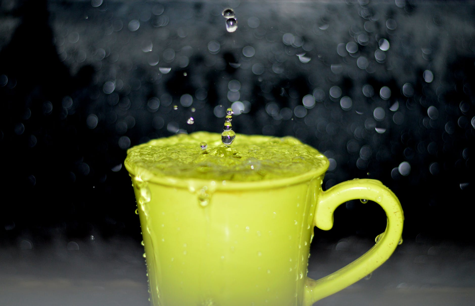 Water falls from a neon yellow cup