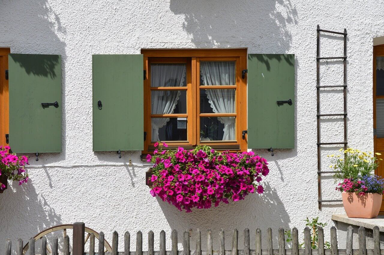 A house with green painted shutters and floral window boxes to boost curb appeal.