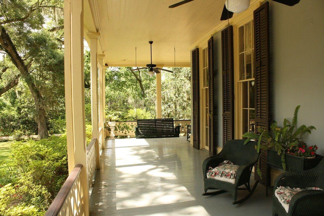 A porch with furniture, a porch swing, and plants to boost curb appeal.