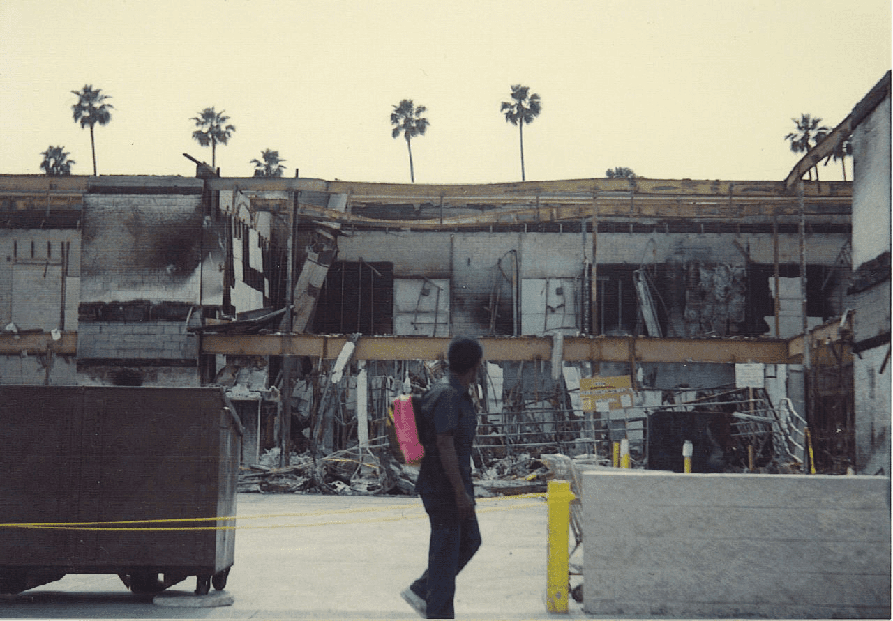 Photo of man looking at destruction following the LA riots of 1992