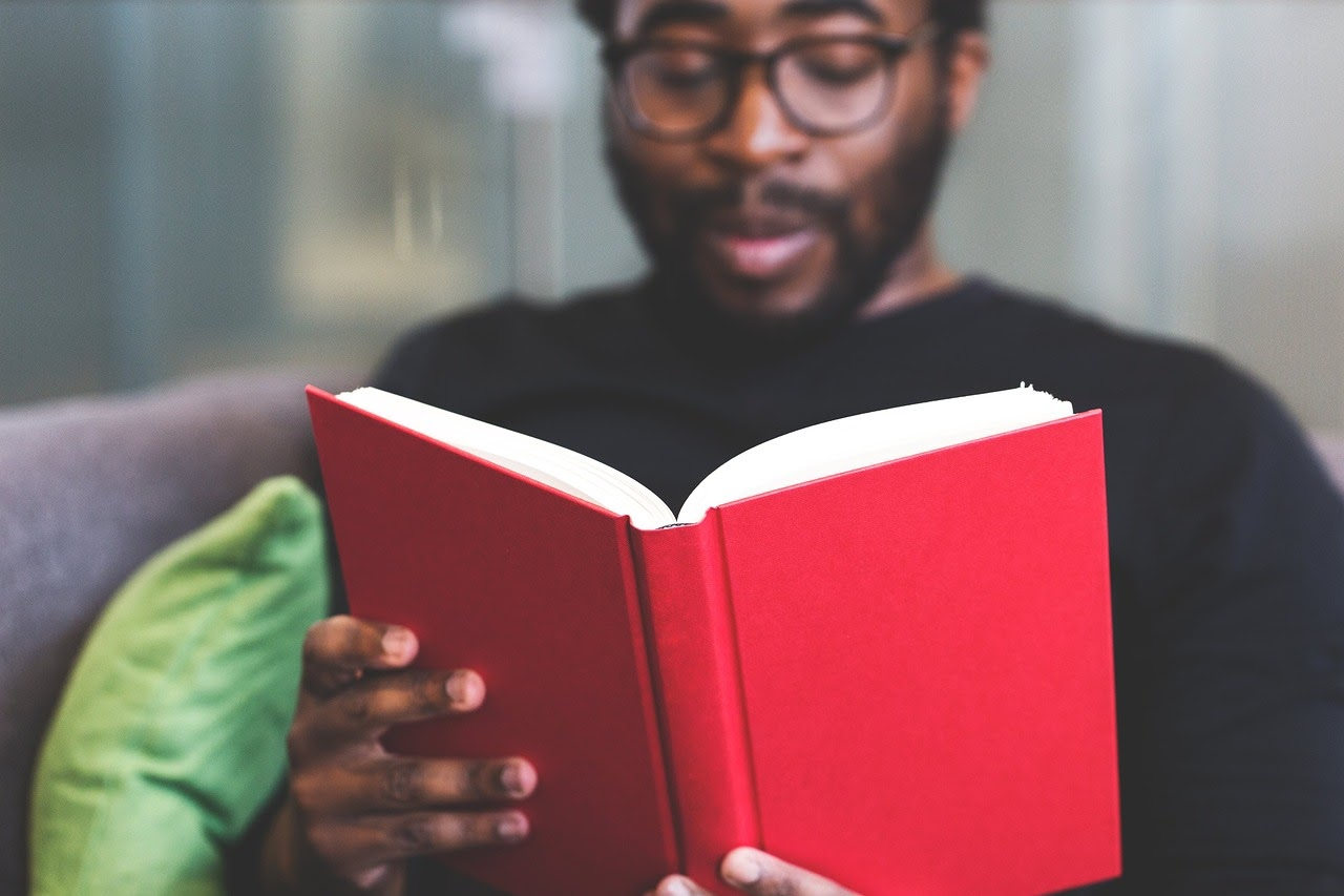 A graduate uses his time during the pandemic to read a book.