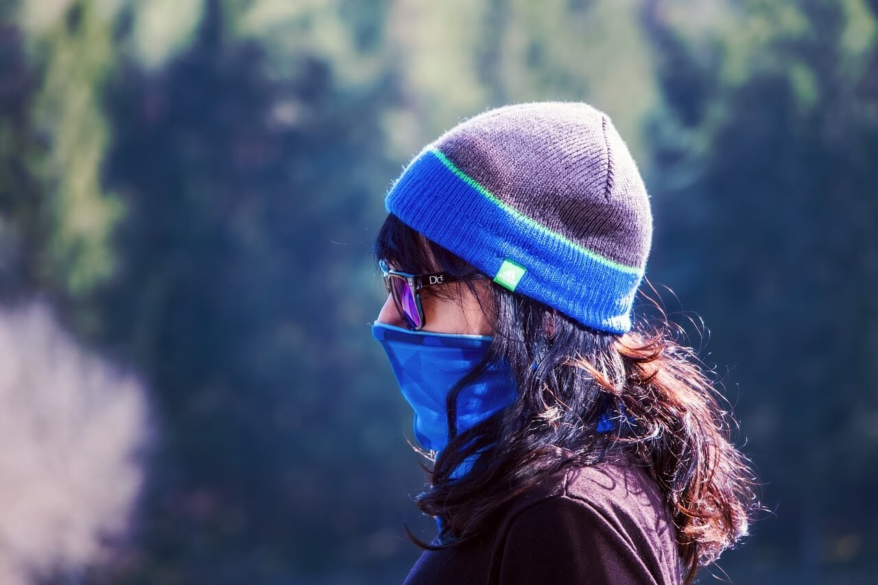 A graduate stands outside wearing a face mask.