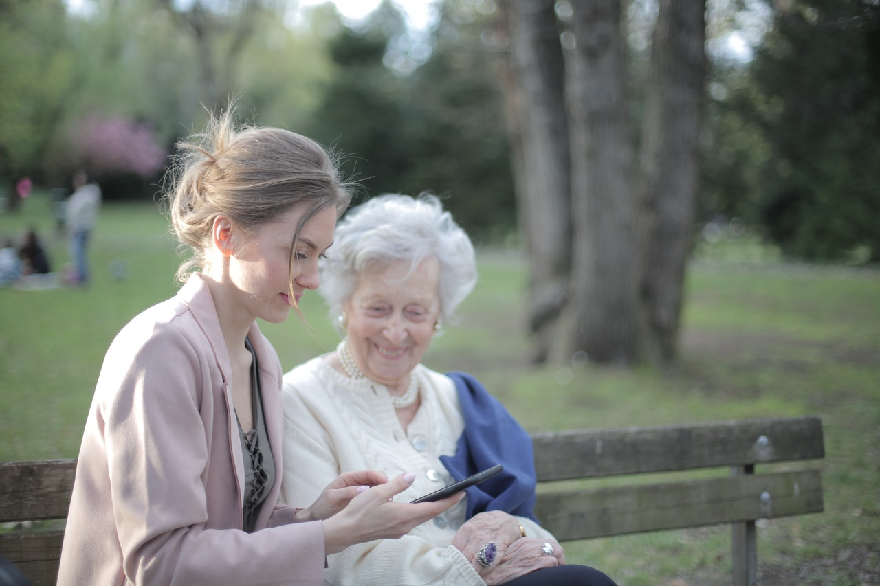 a young woman sits with an older woman on a bench