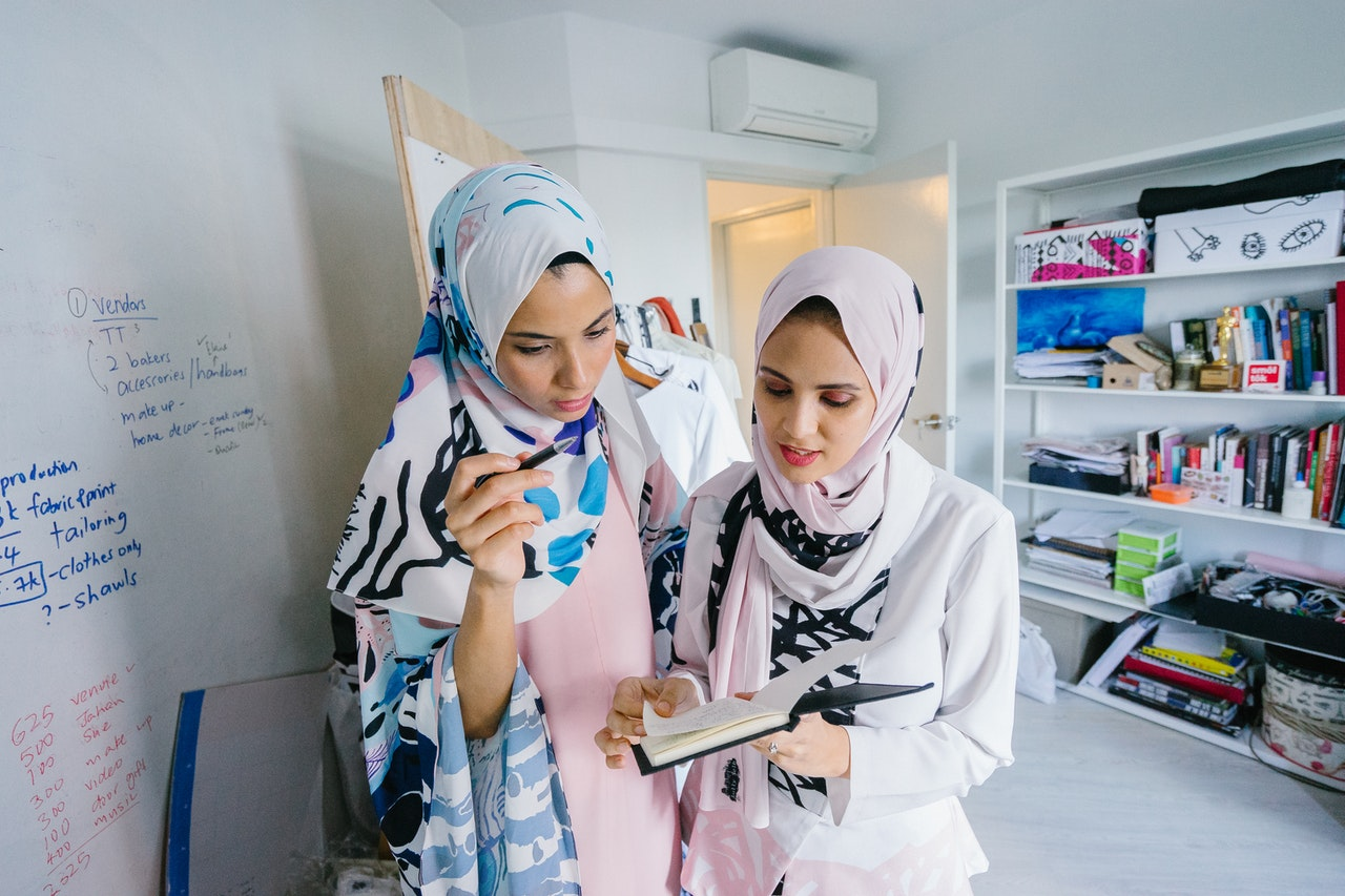 2 women in hijab look over some notes