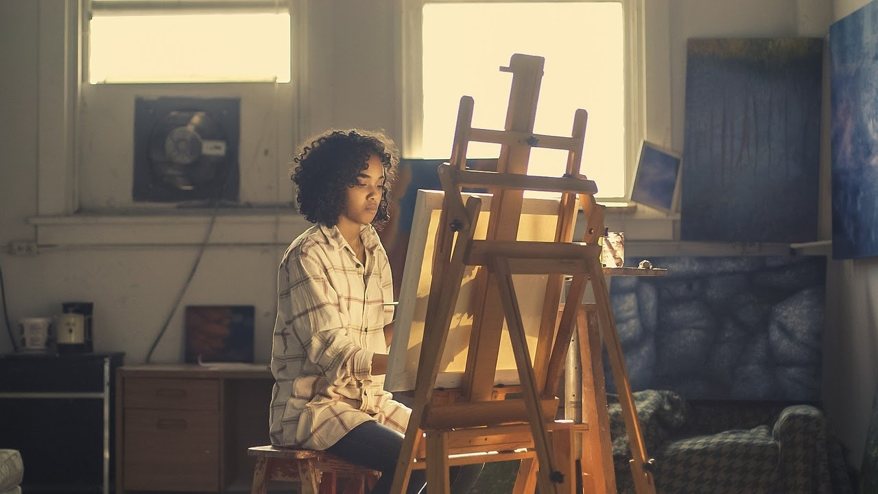 A creative woman paints on an easel.