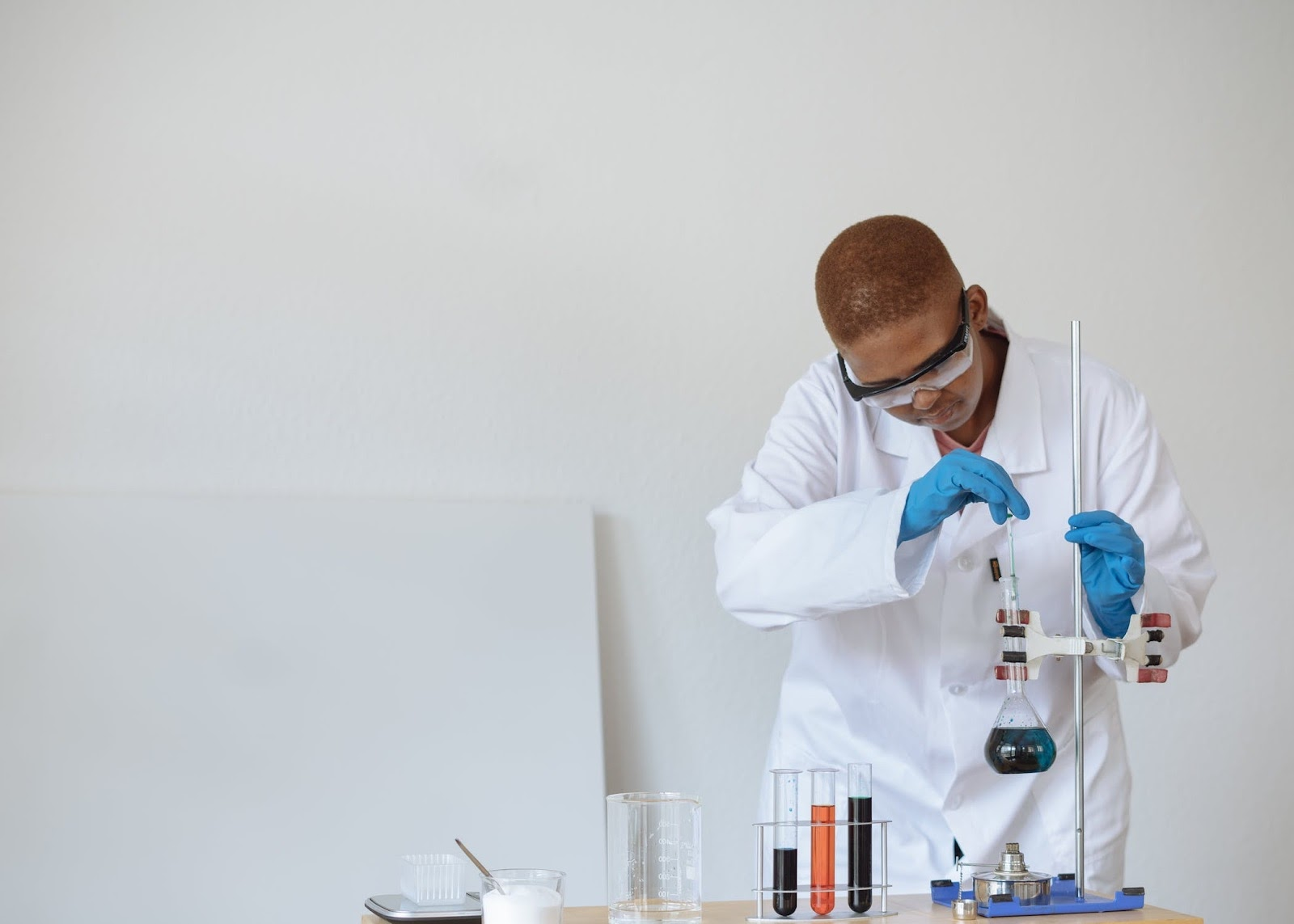 Photo of student in lab coat working in chemistry lab