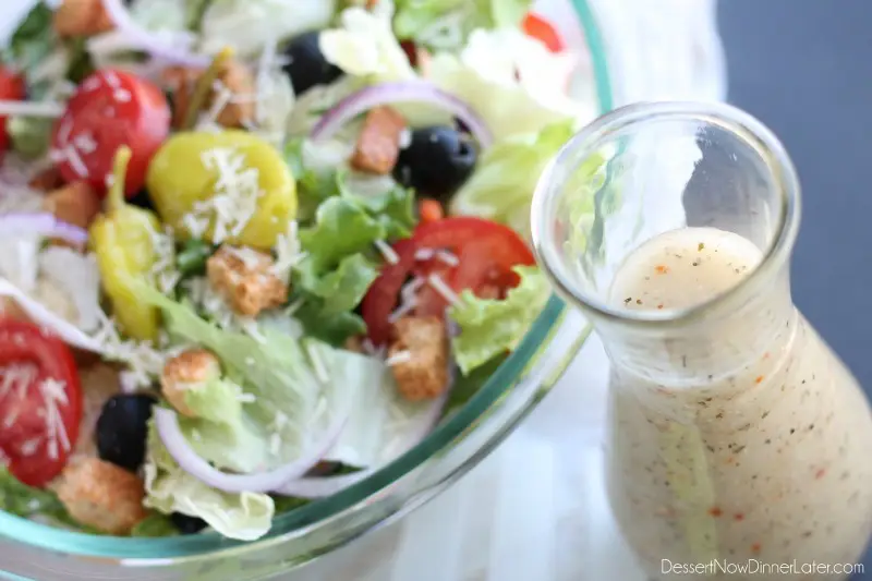 A jar of dressing and a fresh salad