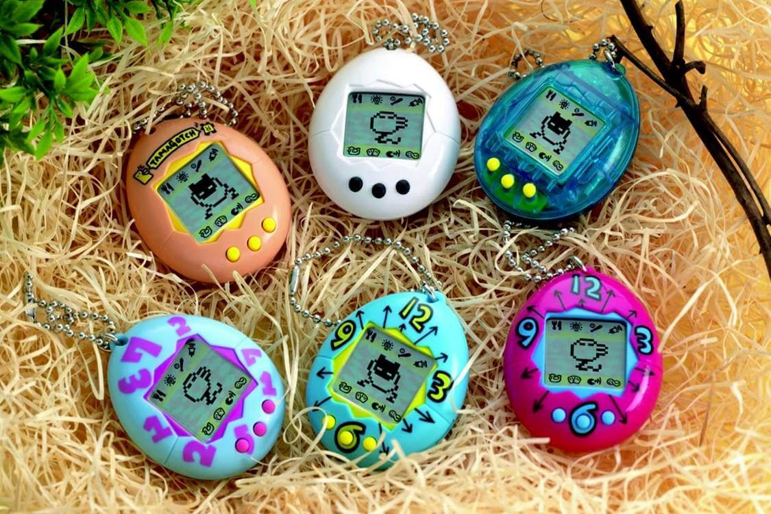 Photo of six Tamagotchi keychains on bed of paper grass