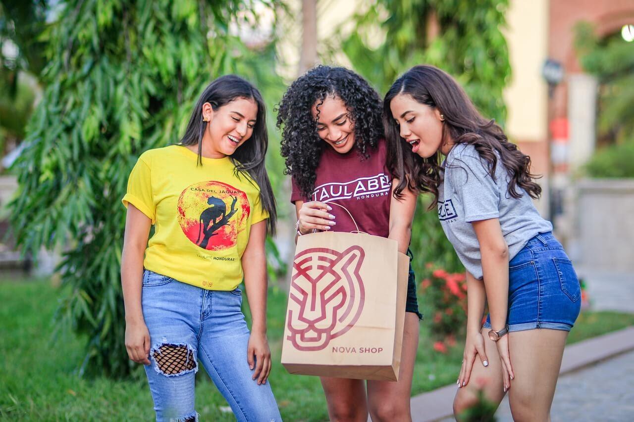 Three women in their 20s look inside a shopping bag.