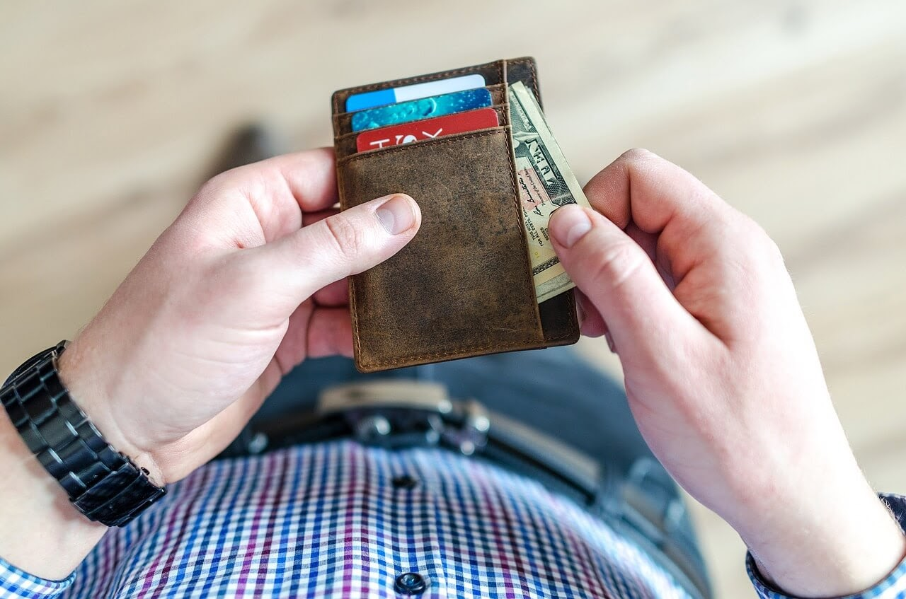 A person pulls money out of a wallet.