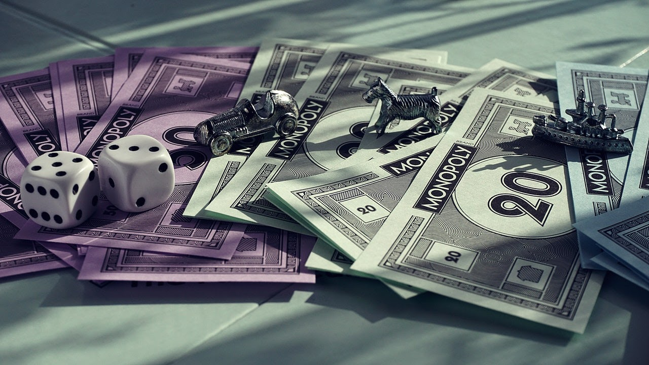 Monopoly money, dice, and playing tokens sit on a table.