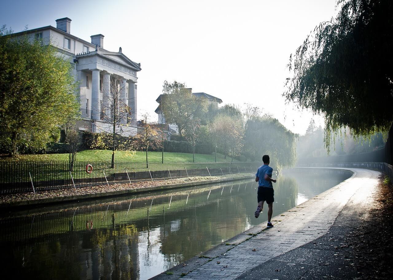 A man runs along a waterway while training for a virtual race.