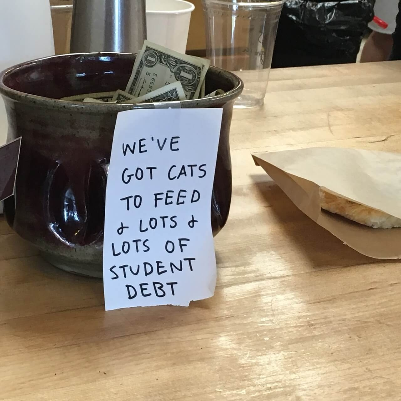 A tip jar for college students sits on a coffee shop counter.